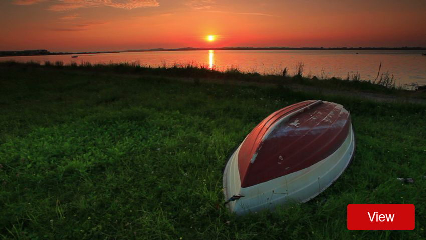 Overturned boat with grassy riverside sunset