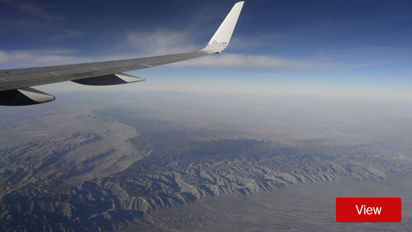 Window view of an airplane wing over mountains