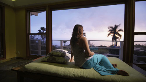 Stock image of a woman sitting on bed overlooking a beautiful sunset