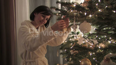 Woman hanging Christmas ornaments stock footage