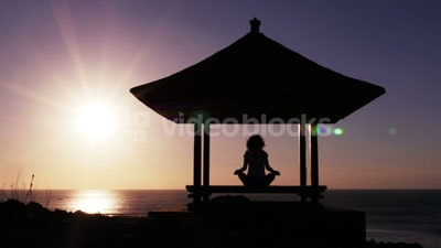 Woman meditating with the sunset in the background stock footage