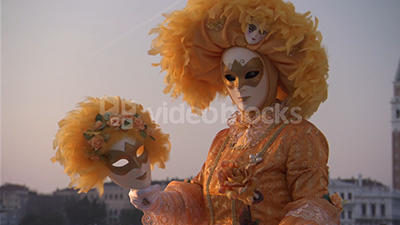 A performer is dressed in a orange feathered costume for the Carnival of Venice