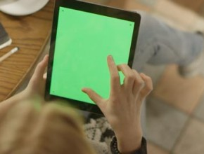 Girl Using Tablet With Green Screen Over the Shoulder view