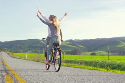 two happy girls riding bike with hands up in the air sunset