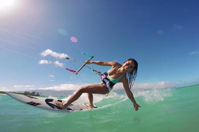 young woman kitesurfing in ocean extreme summer sport