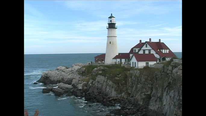 White Lighthouse on Tip of Rocky Shore Stock Photo