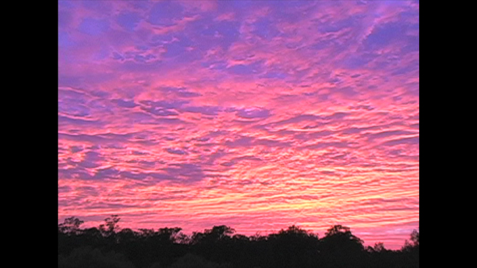 Pink and yellow clouds at sunrise Stock Photo