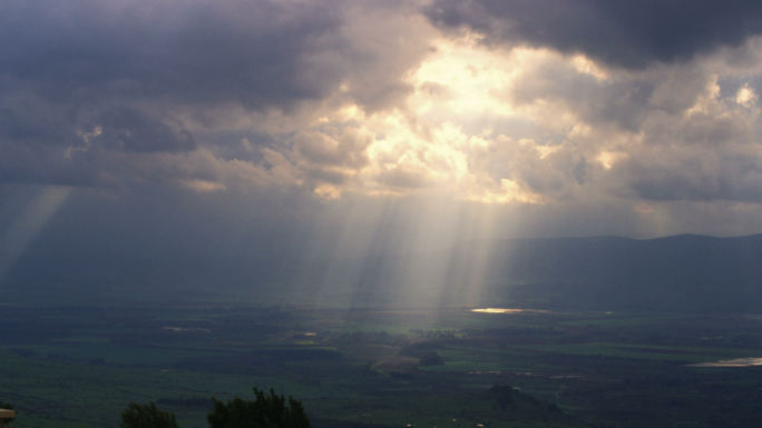 Light Shining Down Through Clouds On Valley Stock Photo