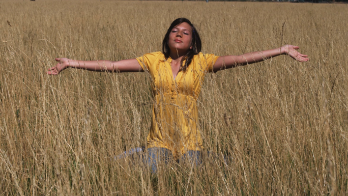 Girl in Yellow Shirt Sits in a Wheat Field 2 Stock Photo