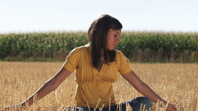 Girl in Sits in a Wheat Field in Front of Corn 4 Stock Photo