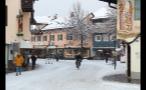 Man Riding Bike Through Snowfall in German Town