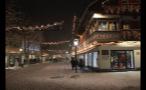 People Walking Through Snowy German Town at Night