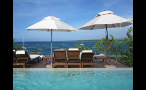 Lounge Chairs and Umbrellas on Pool Deck Overlooking the Water