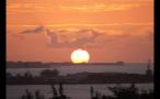 Large Sun Setting on Horizon