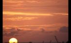 Sun Setting in Orange and Yellow Sky Over Island