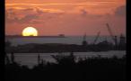 Sun Setting on Horizon and Cranes