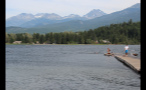 People Swimming In Lake By Mountains