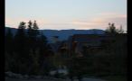 Sun Setting By Homes In Mountains