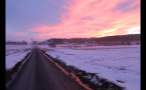 Pink and Yellow Sky Over Snow Covered Farm