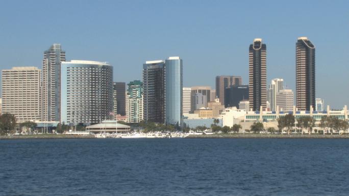 San Diego Harbor Boat Speeds through Skyline in Distance