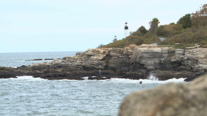 Lighthouse on rocks in distance