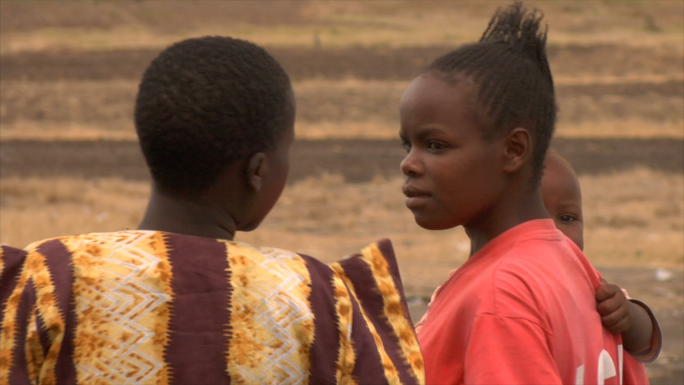 African Women Hold Children and Walk