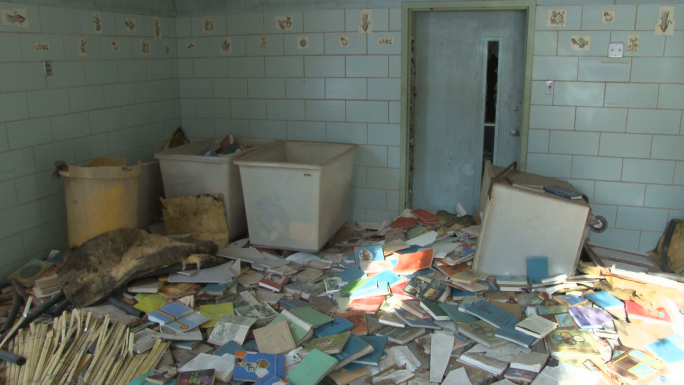 Slow tilt down room covered with forgotten books, dirt and debris.