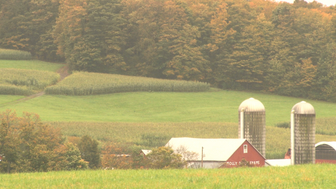 Red Barn With Silos Tucked Into Country Hillside