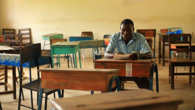 School Boy Doing Homework in Empty Classroom