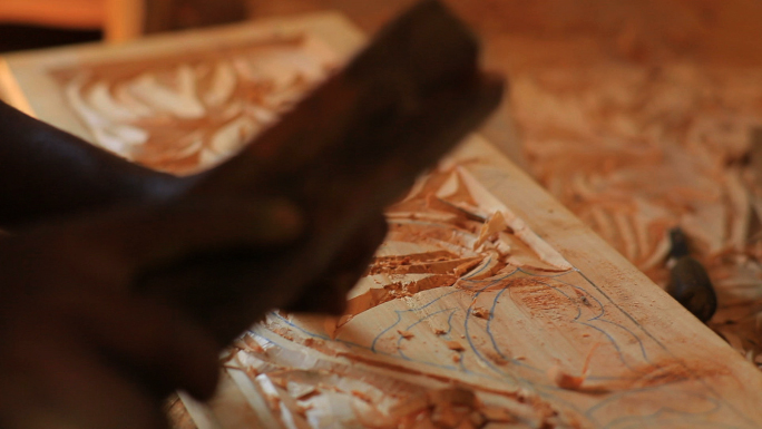 Closeup of Man Chiseling Designs Out of Wood