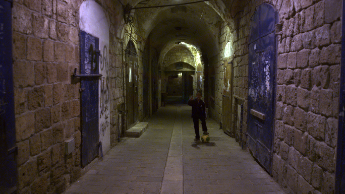 Boy Kicking Soccer Ball In Arched Alley At Night 3