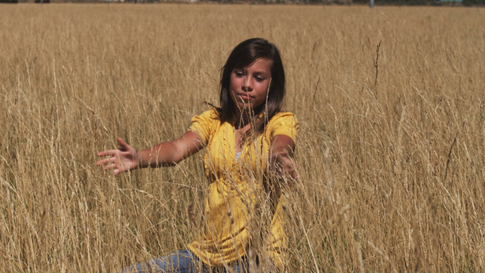 Girl in Yellow Shirt Sits in a Wheat Field