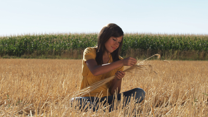 Girl in Sits in a Wheat Field in Front of Corn 5